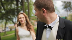 Happy bride and groom walking in the park in summer day. Loving wedding couple Stock Footage