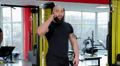 Successful sportive man with fit strong body talking over phone in the gym Footage