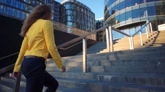 Slow motion. Young beautiful girl in a yellow jacket coming up the stairs Stock Footage