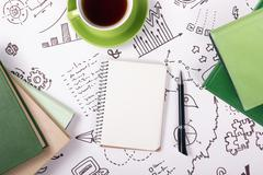 Office table desk with supplies, blank note pad, cup, pen on white background of Stock Photos