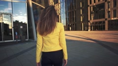 Slow motion. Camera following to Young beautiful girl in a yellow jacket which Stock Footage