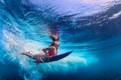 Beautiful surfer girl diving under water with surf board Stock Photos