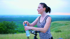 Girl drinks water from a bottle for sports riding a fitness bicycle Stock Footage