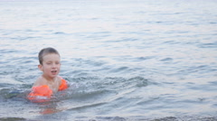 Boy Playing on Waves on the Beach in Inflatable Armbands in Twilight Stock Footage