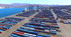 Flying above cargo containers and auto-loaders driving between them in East Port - stock footage