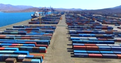 Flying above cargo containers and auto-loaders driving between them in East Port Stock Footage