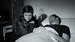 Sad woman crying in hospital holding hand of sick boyfriend at night black an Stock Footage