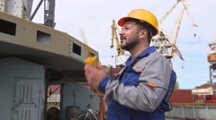 Dock worker with yellow helmet and walkie-talkie directs the cargo crane in Stock Footage