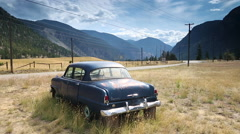 Abandoned old Plymouth car by road with traffic, nr Vancouver, British Columbia Stock Footage