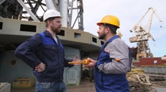 Dock worker and engineer have serious talk, then laugh and give high five in Stock Footage