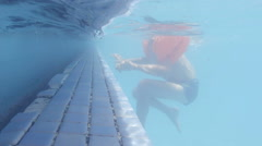 Underwater shot of little boy in arm bands learning how to swim Stock Footage