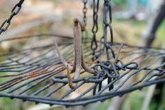 Rusty iron triple hook on grate hanging on chains. Shallow depth of field. Stock Photos