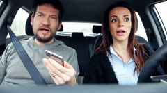 Man and woman in car talking to friend on the phone while driving Stock Footage