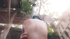 Woman taking a shower on nature - stock footage