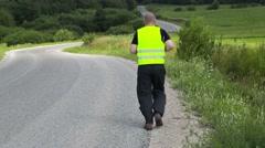 Runner on highway slowly run away Stock Footage