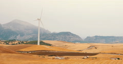 Wind turbine set in rustic dry fields on a hazy day with old farm house in FG Stock Footage