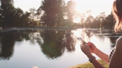 Woman Relaxes by the Sunny Lake Texting on Smartphone. SLOW MOTION 120 fps 4K Stock Footage