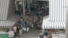 Jean-Talon market rooftop above interior alley, people walks and shops groceries Stock Footage