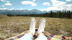 Legs of traveler sitting on a high mountain top in travel. Freedom concept Stock Footage