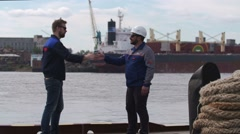 Two good friends, dockers and colleages give high five and say goodbye in Stock Footage