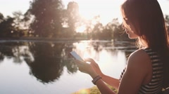 Woman Relaxes by the Sunny Lake Using Smartphone. SLOW MOTION 120 fps 4K Stock Footage