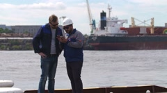 Two good friends, dockers and colleages look at smartphone in Shipping cargo Stock Footage