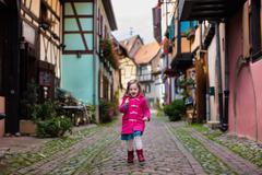 Little girl in historical city center in France Stock Photos