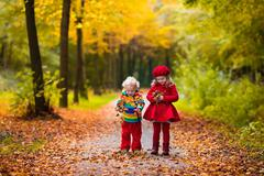 Kids playing in autumn park Stock Photos