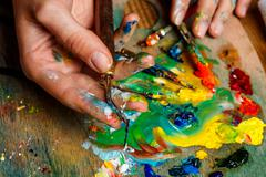 Close up photo of girl mixing oil paints on palette Stock Photos