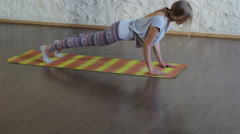 The young blonde girl practicing yoga in a hall. Pose of cobra. Pose of plank HD Stock Footage