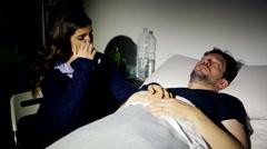 Sad woman in hospital holding hand of sick boyfriend Stock Footage