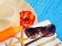 Beach hat, sunglasses, bath towel, sun spray, starfish. Stock Photos
