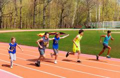 Five teenage sprinters running with German flag Stock Photos