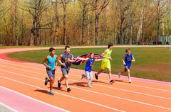 Teenage track sprinters running with British flag Stock Photos