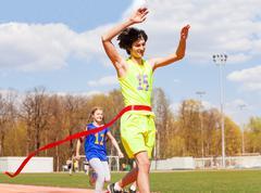 Happy teenage winner crossing the finish line Stock Photos