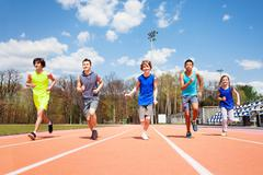 Five teenage sprinters running together on a track Stock Photos