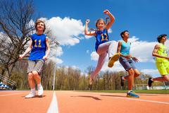 Happy teenage athletes running in the stadium Stock Photos