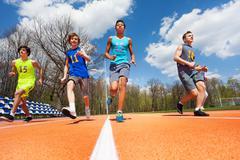 Athletics teenage boys running on the racetrack Stock Photos
