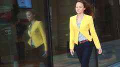 Focus on the reflection. Slow motion. Young business woman in yellow jacket Stock Footage