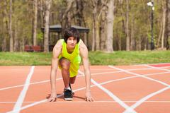 Young sporty boy in start position at racetrack Stock Photos