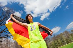 Portrait of teenage sportsman waving German flag Stock Photos