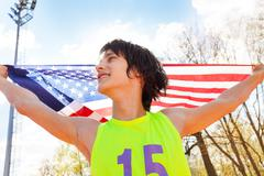 Portrait of young champion waving American flag - stock photo