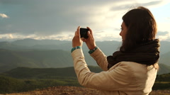 Young woman traveler on a background of mountains takes photos on a mobile phone Stock Footage