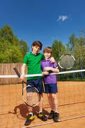 Two tennis winners standing next to the net Stock Photos