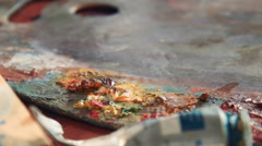 Close up details of yellow oil paint on an artists pallet Stock Footage