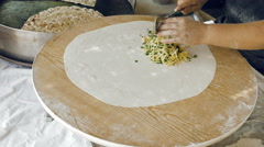 Woman's hands putting filling and oil on the dough Stock Footage