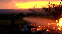 View of fireman spraying hose on fire where house burned down at sunset. Stock Footage