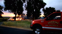 Fire department truck with lights flashing as house fire is in the background. - stock footage