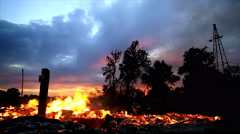 Remains of house on fire after it has burned to the ground at sunset. Stock Footage