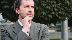 Stressed business man hard thinking outdoors in green park near office building Stock Footage